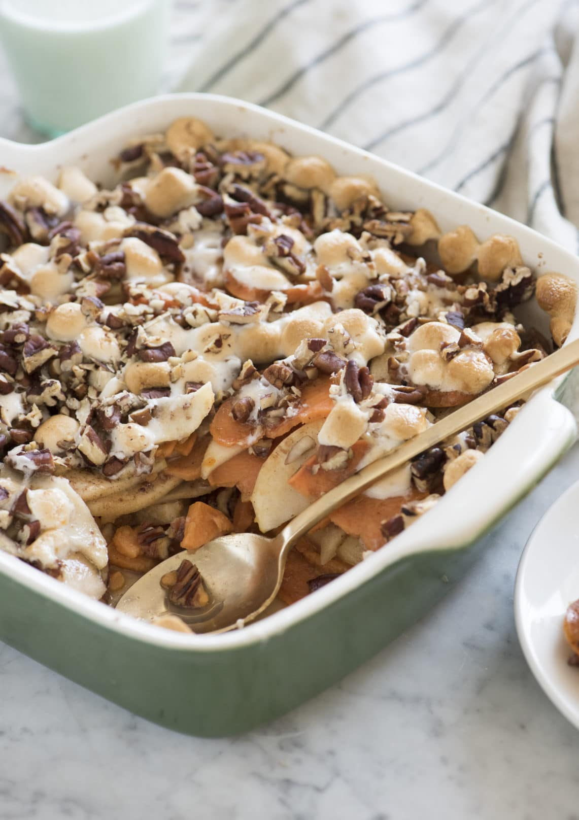 sweet potato casserole in a green dish with a gold spoon scooping out filling