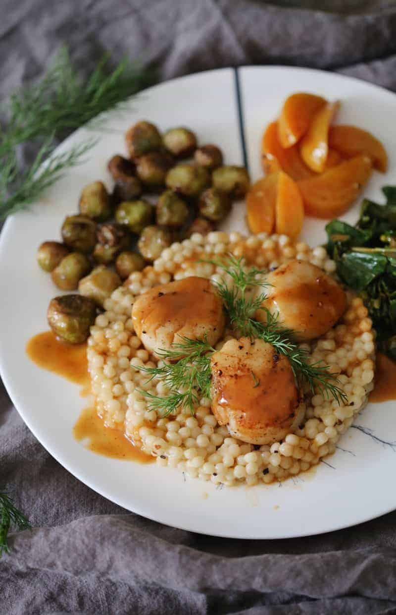 A delicious scallop dish with cous cous, brussels sprouts, and beets.