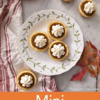 Five mini pumpkin pies on a marble counter.