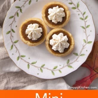 Three mini pumpkin pies with whipped cream on a plate.