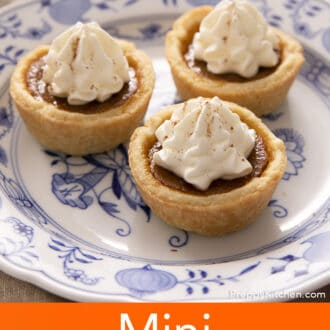 Three mini pumpkin pies topped with whipped cream on a small plate.