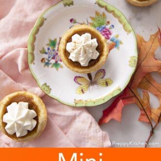 Mini pumpkin pies next to a pink napkin.