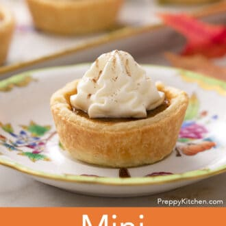 A mini pumpkin pie topped with a dollop of whipped cream on a porcelain plate.