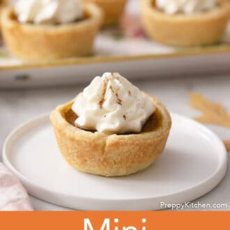 A mini pumpkin pie with whipped cream on a white plate.