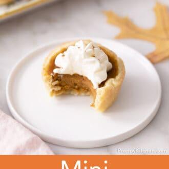 A mini pumpkin pie with a bite taken out.