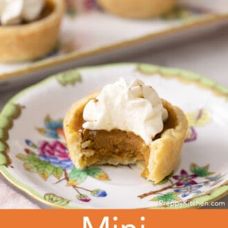 A mini pumpkin pie on a plate with a bite taken out.