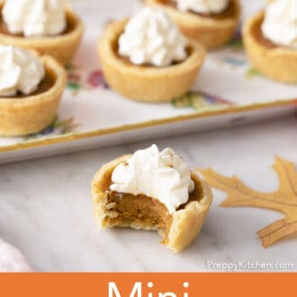 A group of mini pumpkin pies, the one in the foreground has a bite taken out.