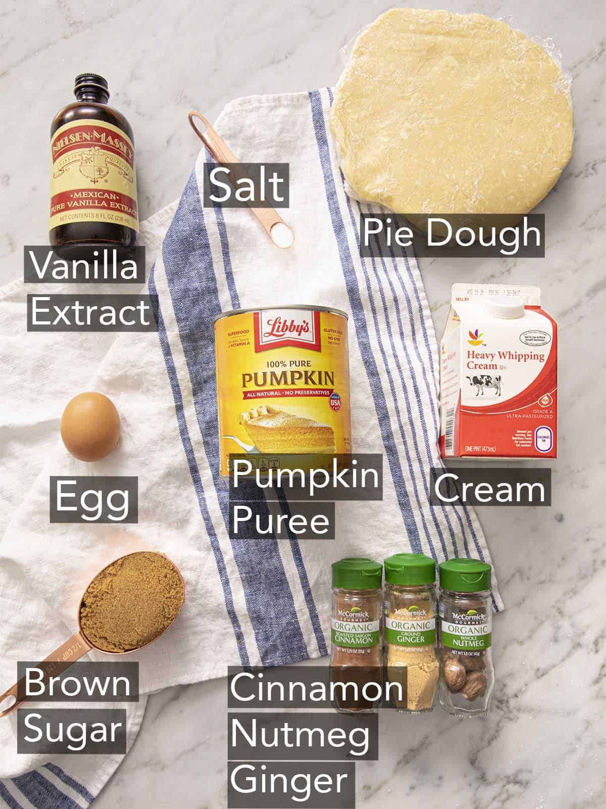 Ingredients for making mini pumpkin pies on a marble counter.