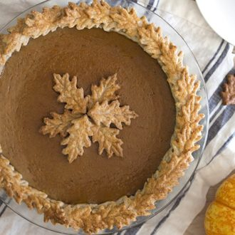 Photo of a pumpkin pie with pastry leaves on a blue and white linen.