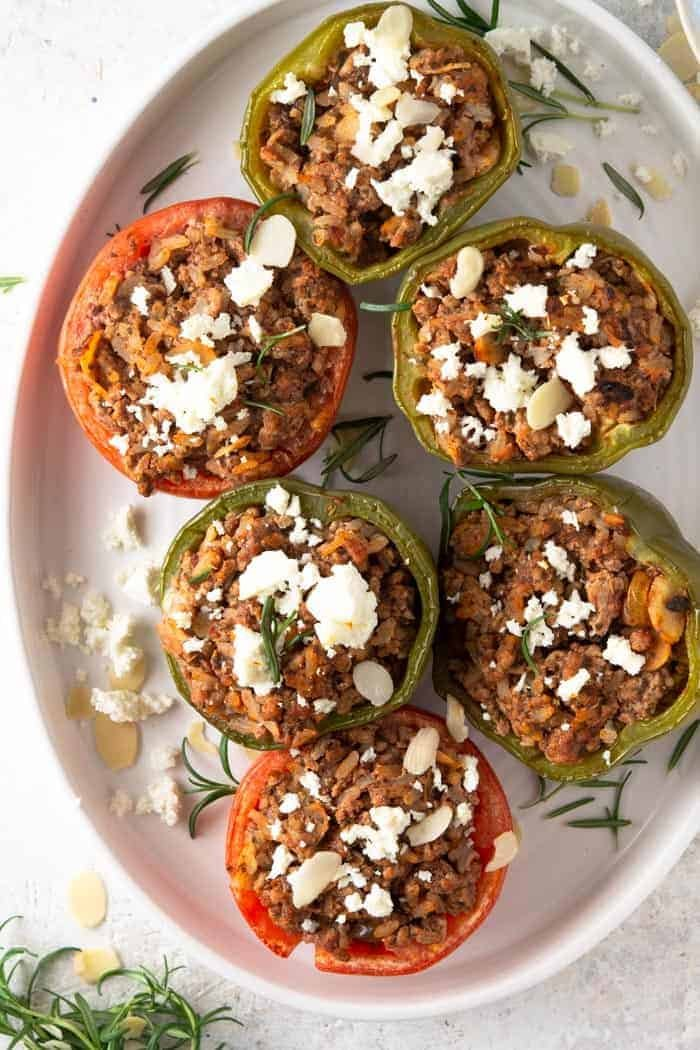 A photo of the top of stuffed tomatoes and peppers topped with feta cheese.