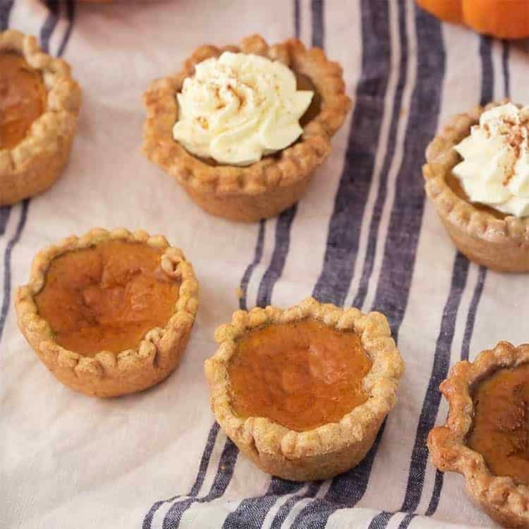 A group of mini pumpkin pies on a striped linen