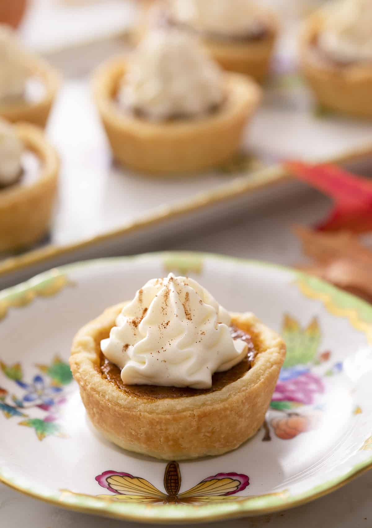Mini pumpkin pies topped with whipped cream on a marble counter.
