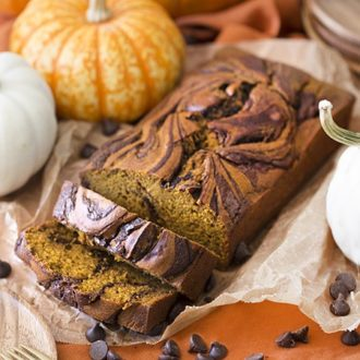 moist pumpkin swirl bread that has been cut into. Displayed with pumpkins and chocolate chips