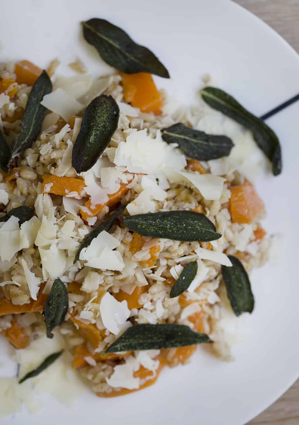 Butternut Squash Risotto on a plate with fried sage leave on top.