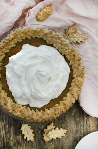 A photo of a sweet potato pie with a large dollop of whipped cream on top.