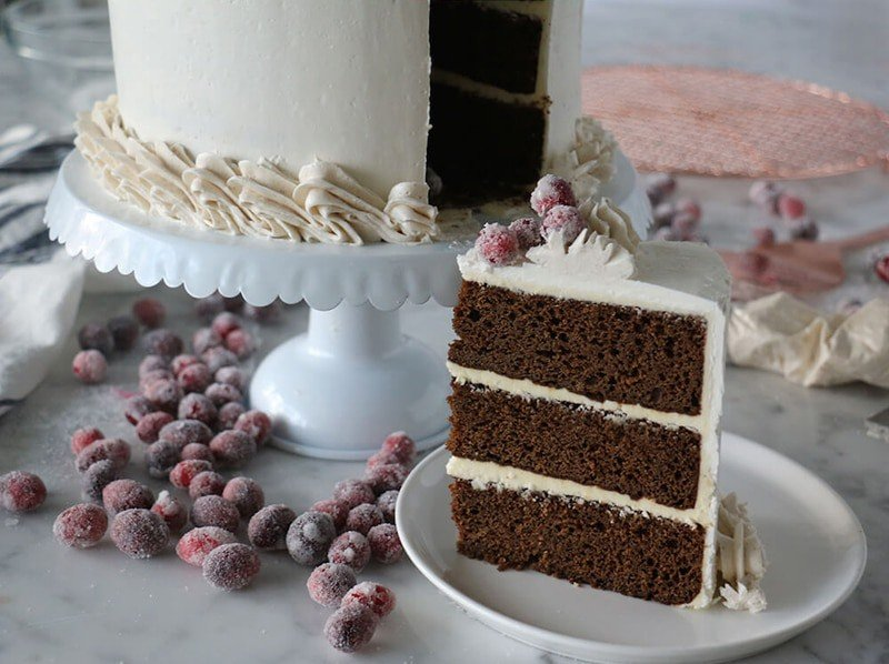A photo showing a slice of gingerbread cake on a plate with the rest of the cake behind it.