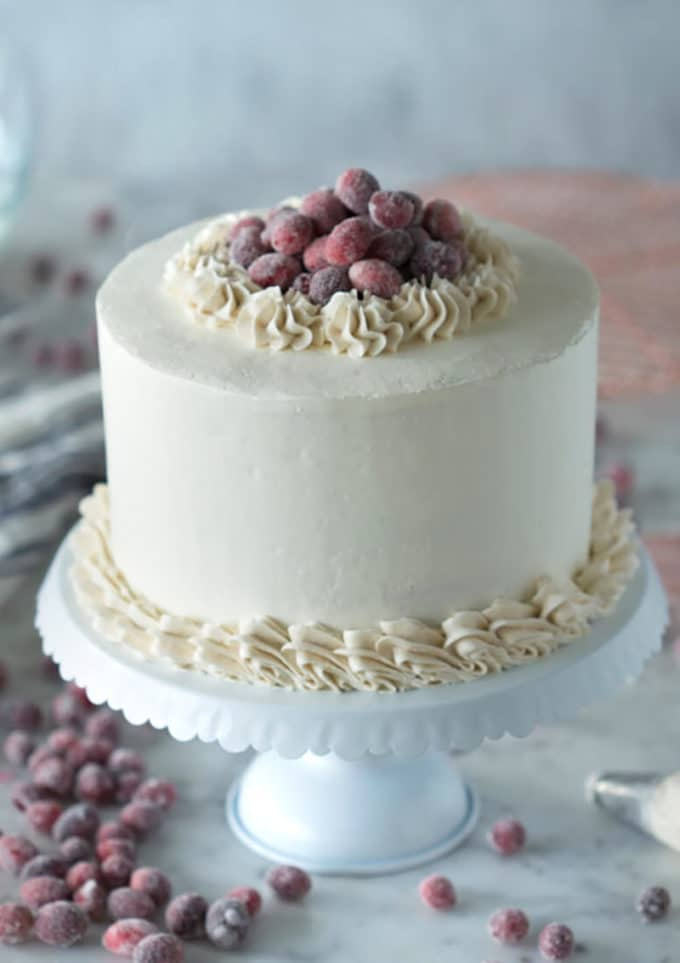 Photo of a gingerbread cake topped with sparkling cranberries on a marble table.