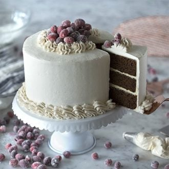 Photo of a Gingerbread Cake topped in sparkling cranberries with a piece coming out.