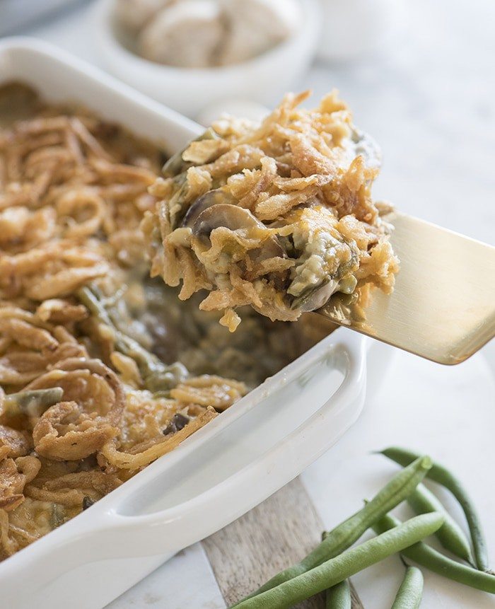 photo of green bean casserole being serves with a gold spatula