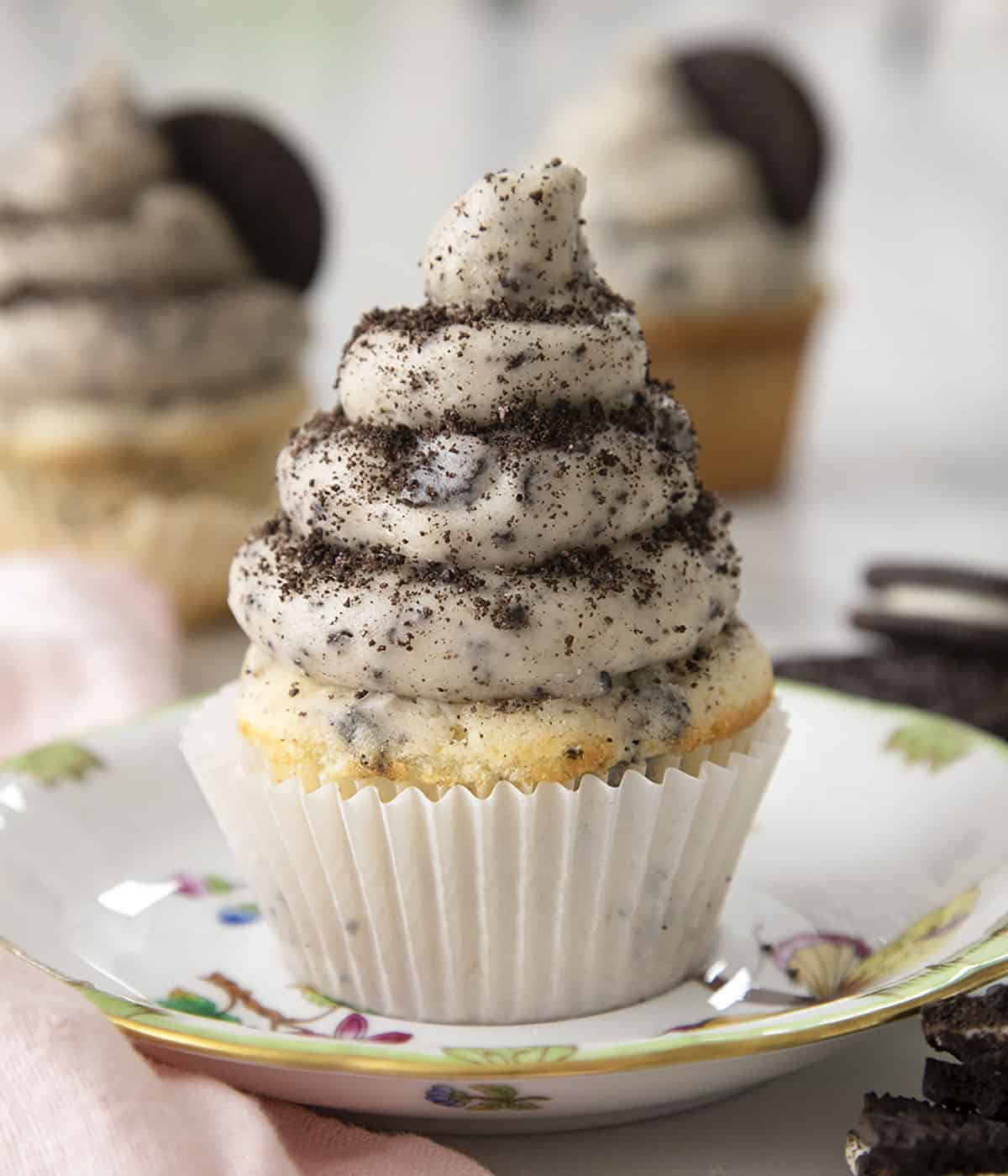An Oreo cupcake topped with a nice swirl of Oreo buttercream on a plate.