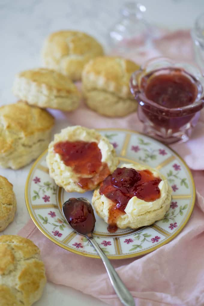 A photo of classic scones on a plate with jam on top.