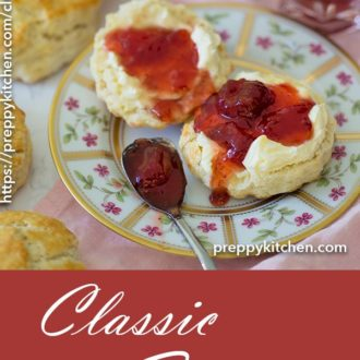 A clipping of classic english style scones on a plate with butter and jam.