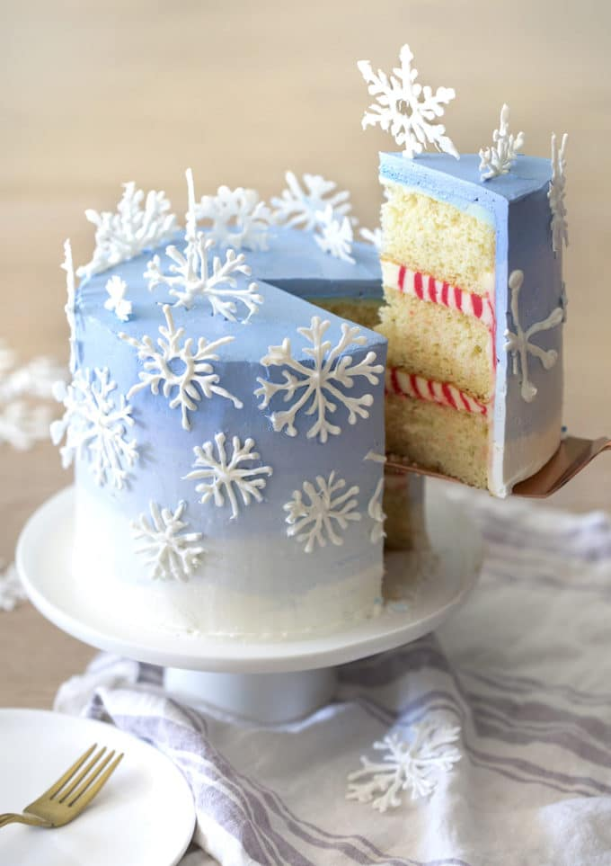 A photo of a piece being removed from a cake with snowflakes on top.
