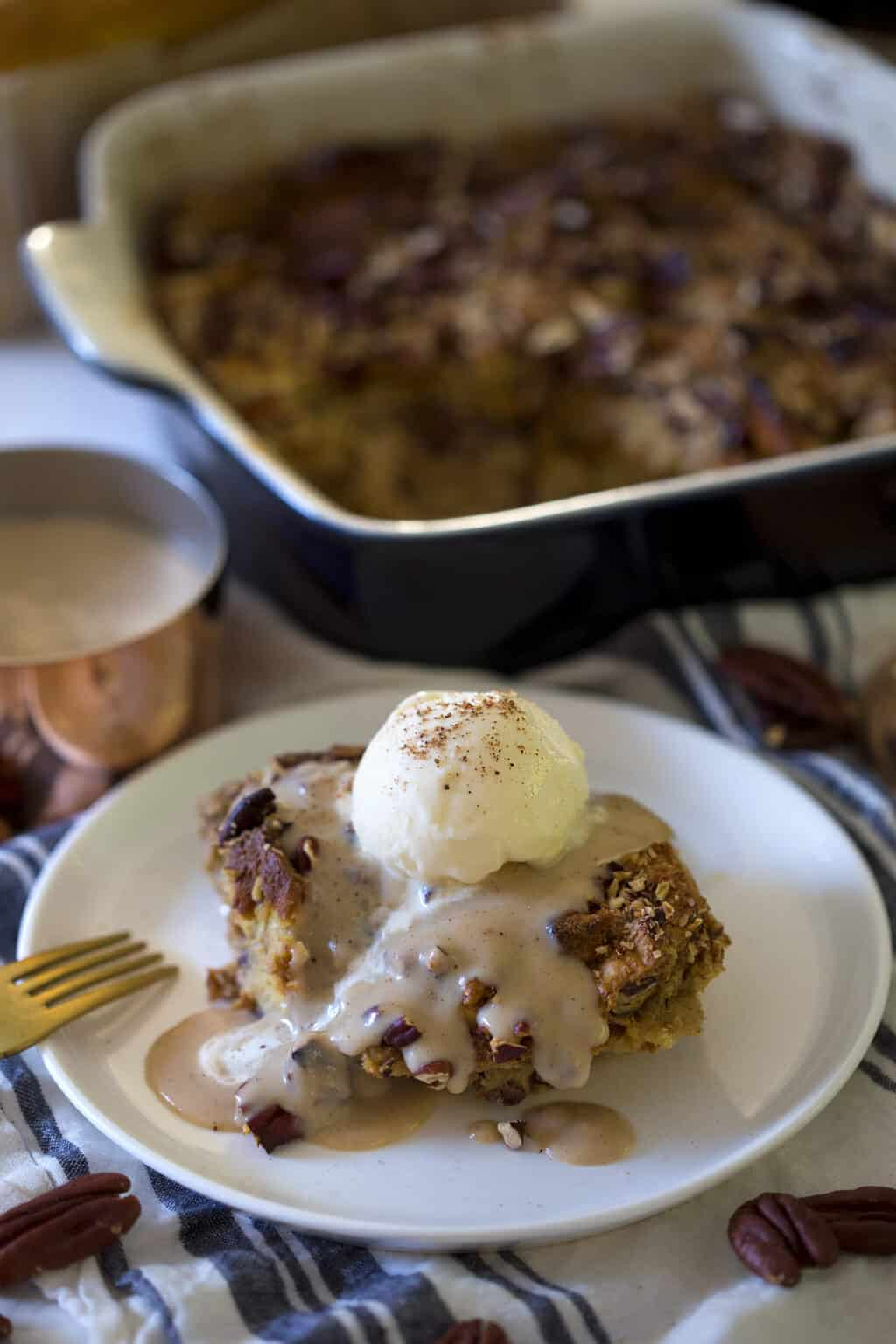 A photo of a piece of bread pudding on a plate with sauce and a scoop of ice cream on top.