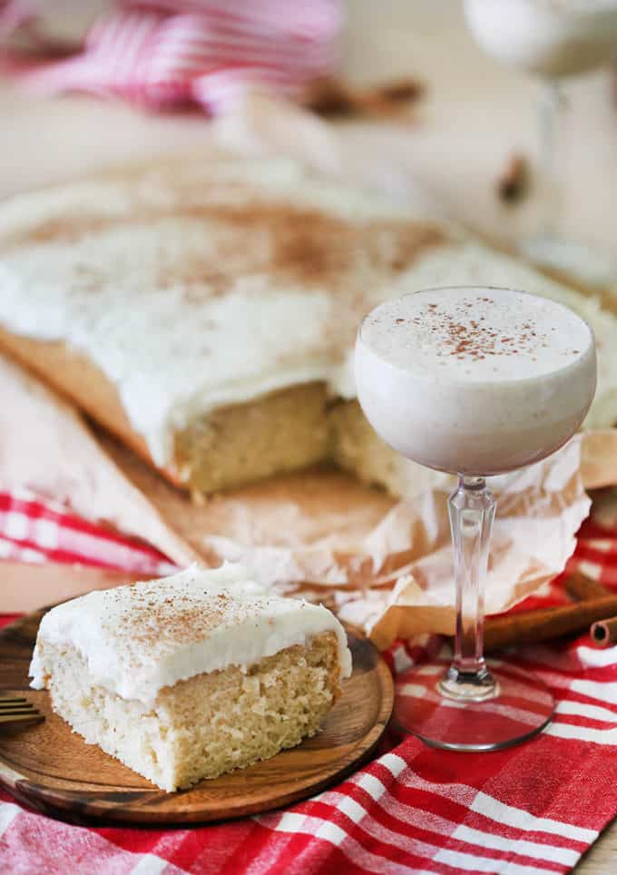 An eggnog sheet cake with a piece in the foreground.