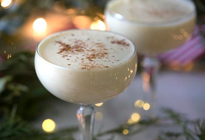 A closeup photo of eggnog cocktails in coupe glasses.