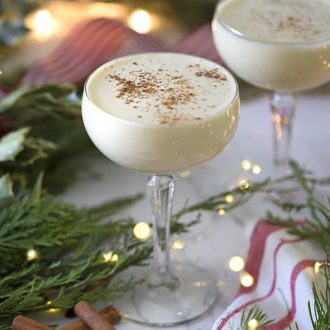 A photo of two eggnog cocktails in a holiday scene