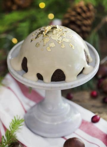 A photo of chocolate Christmas pudding on a mini cake plate with gold flakes on top