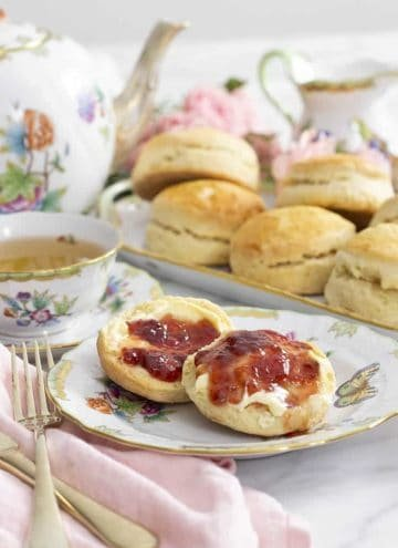 scones on a porcelain plate with a teapot next to them