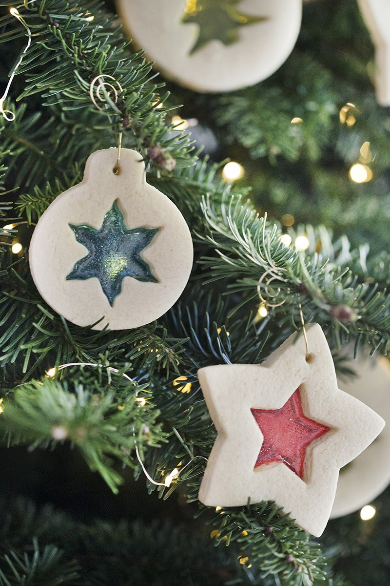 A photo of Christmas ornament cookies hanging on a tree.