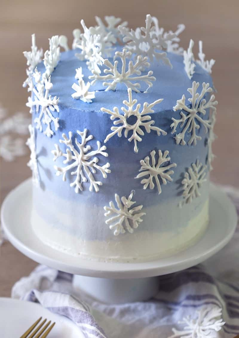 A photo of a blue and white ombre cake with snowflakes on top.