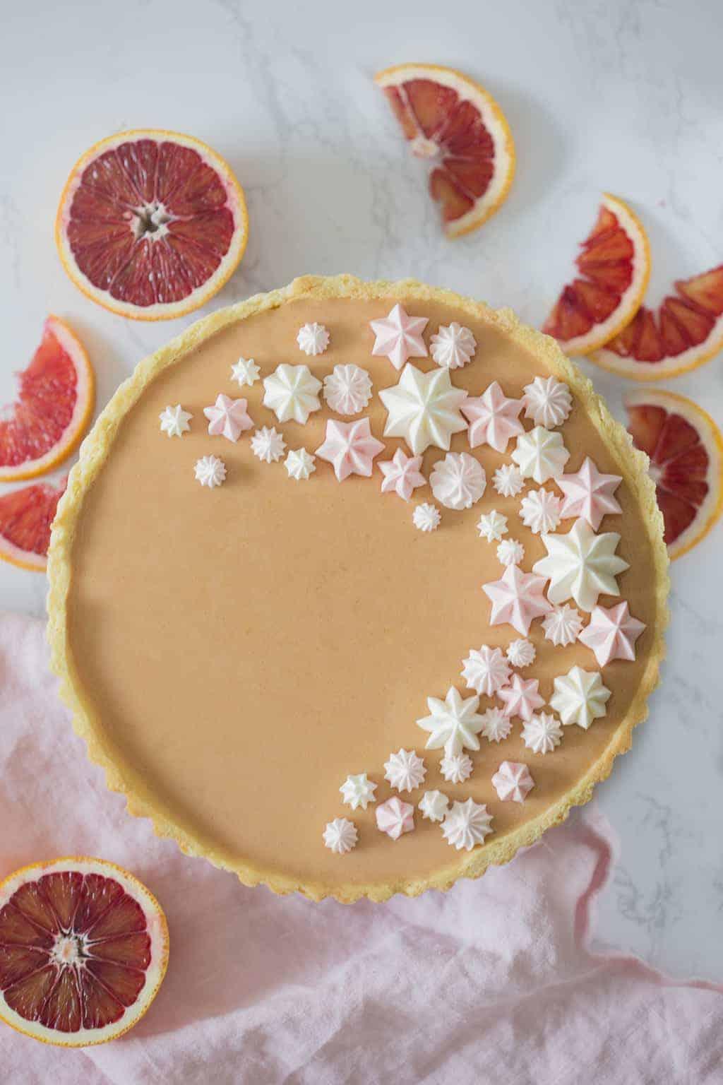 A blood orange curd tart with Swiss buttercream dollops on top.