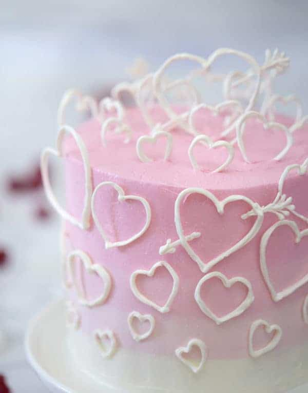 A close up photo of a pink ombré cake covered in white hearts made out of candy melts.