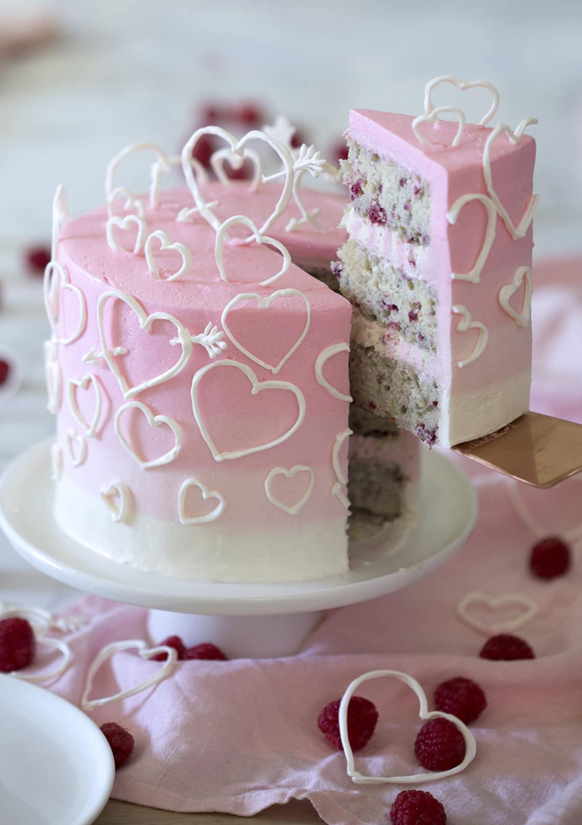 A photo of a Raspberry Valentine's Cake with a piece being removed