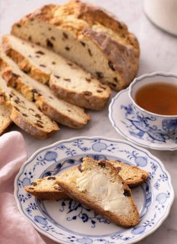 Slices of Irish soda bread spread with butter on a blue plate