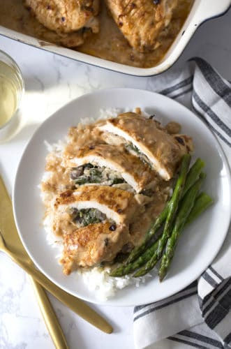 Spinach Stuffed Chicken Breast on a plate with rice and asparagus.