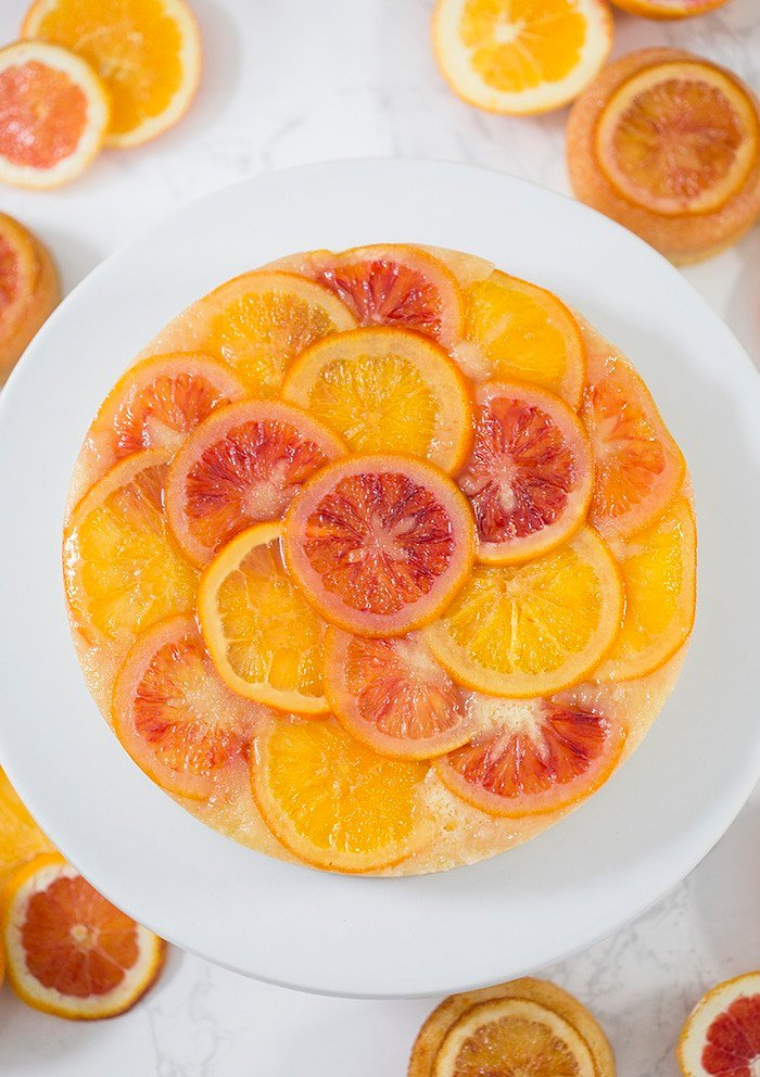 a top down photo of an orange upside down cake on a white cake strand