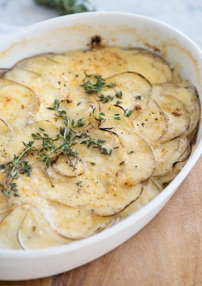 A photo of potato gratin in a white oval casserole dish