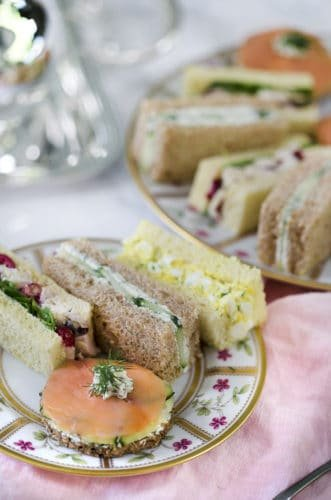 A photo showing English tea sandwiches arranged on a painted porcelain plate
