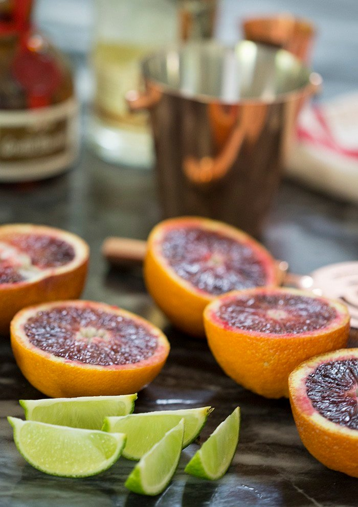 A photo showing cut blood oranges and limes on a black soapstone counter