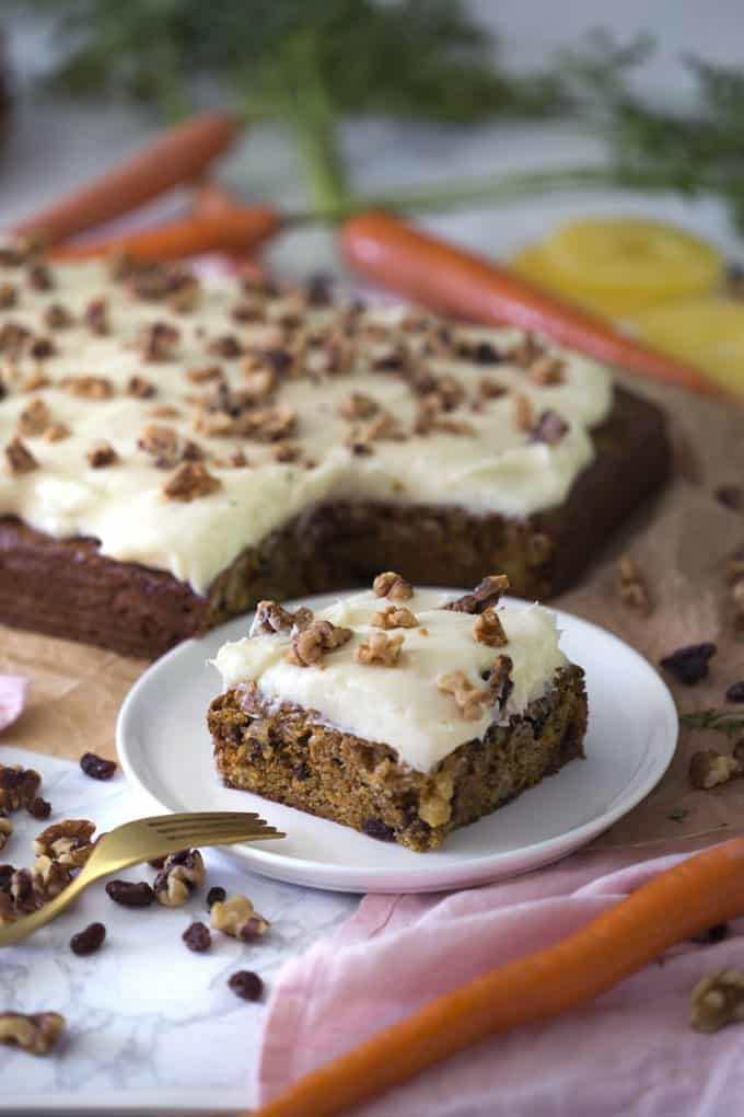 A photo of a carrot and walnut cake with a piece on a plate.