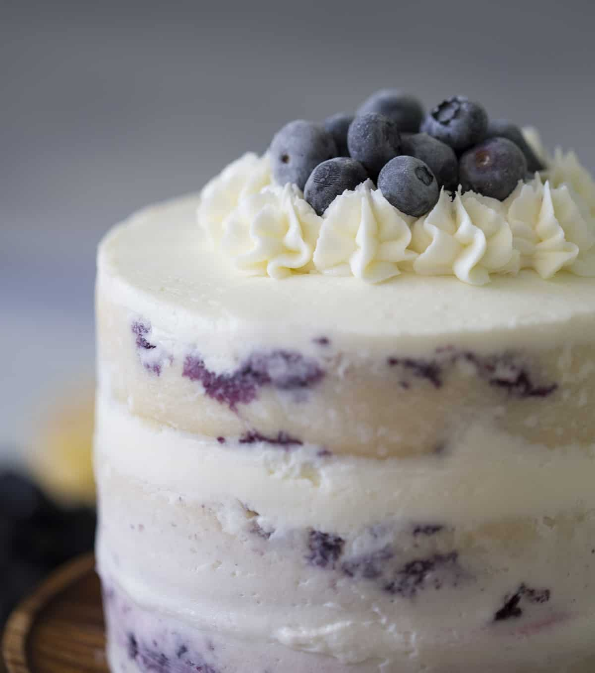 A lemon blueberry cake topped with frozen blueberries.