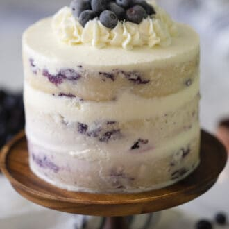 A lemon blueberry cake on a wooden cake stand