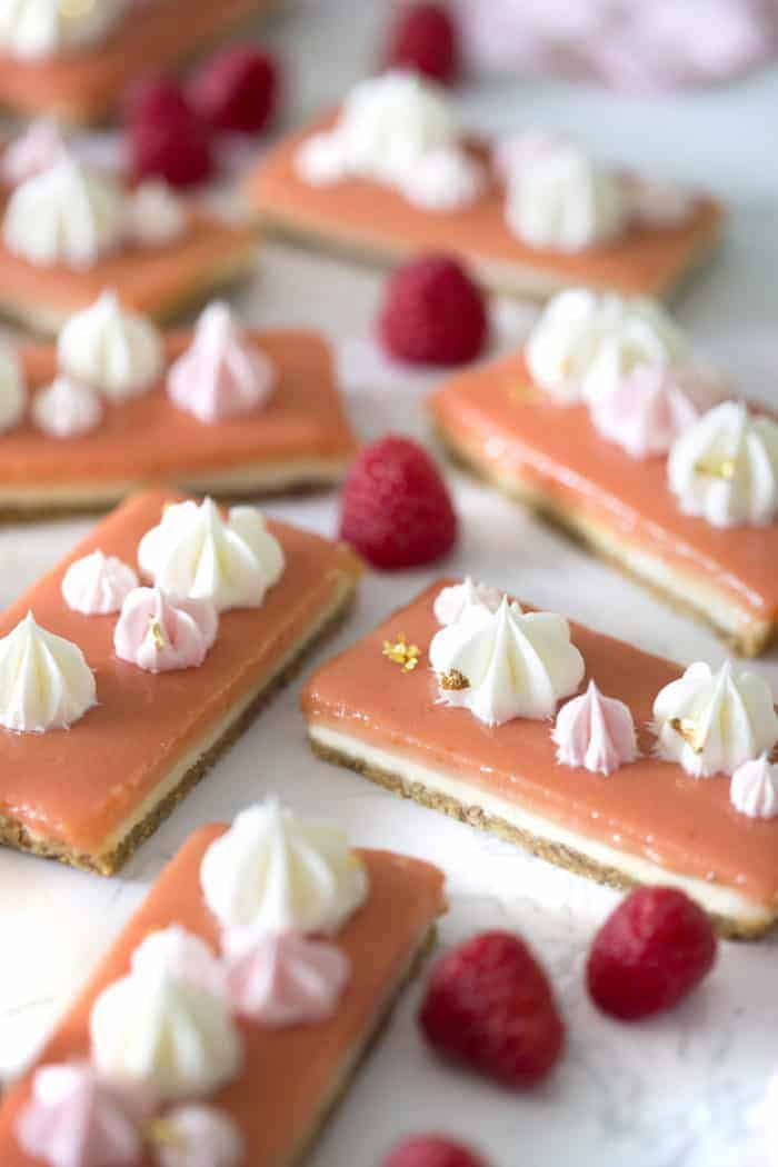 A photo of no Bake Raspberry Cheesecake Bars with dollops of Swiss meringue buttercream on top.