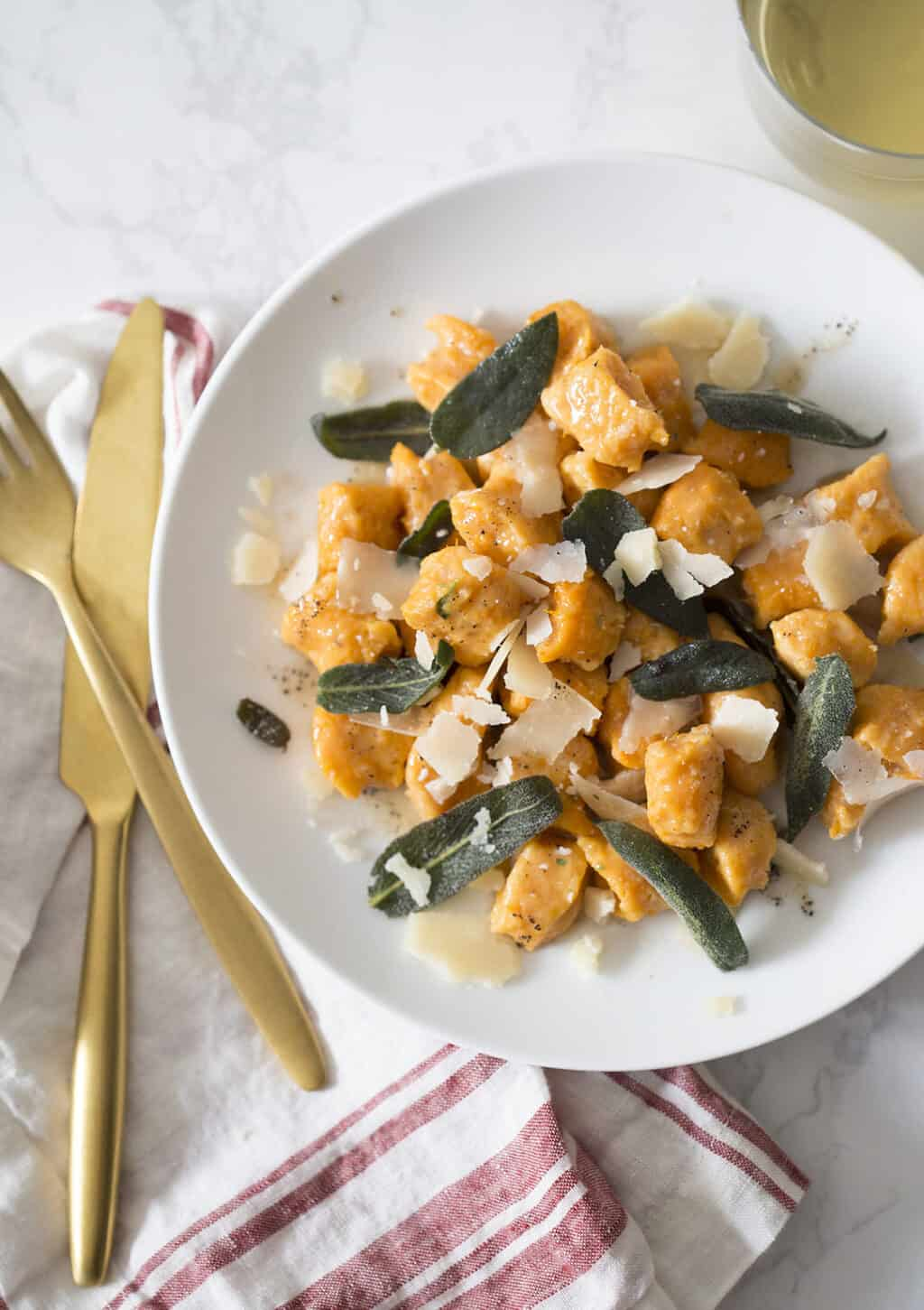 A photo of Sweet Potato Gnocchi in a bowl with sage leaves on top.