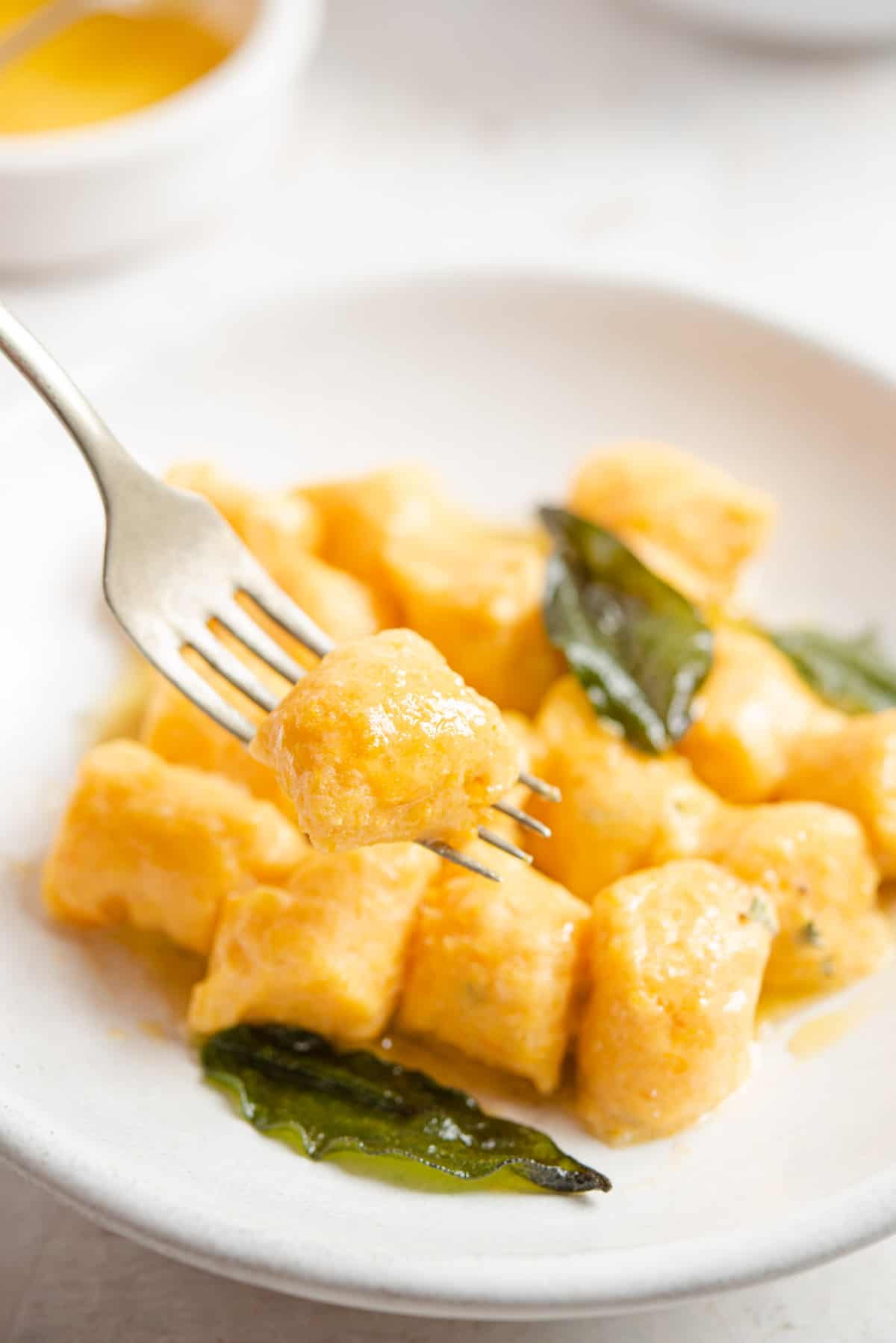 A close up of sweet potato gnocchi on a fork